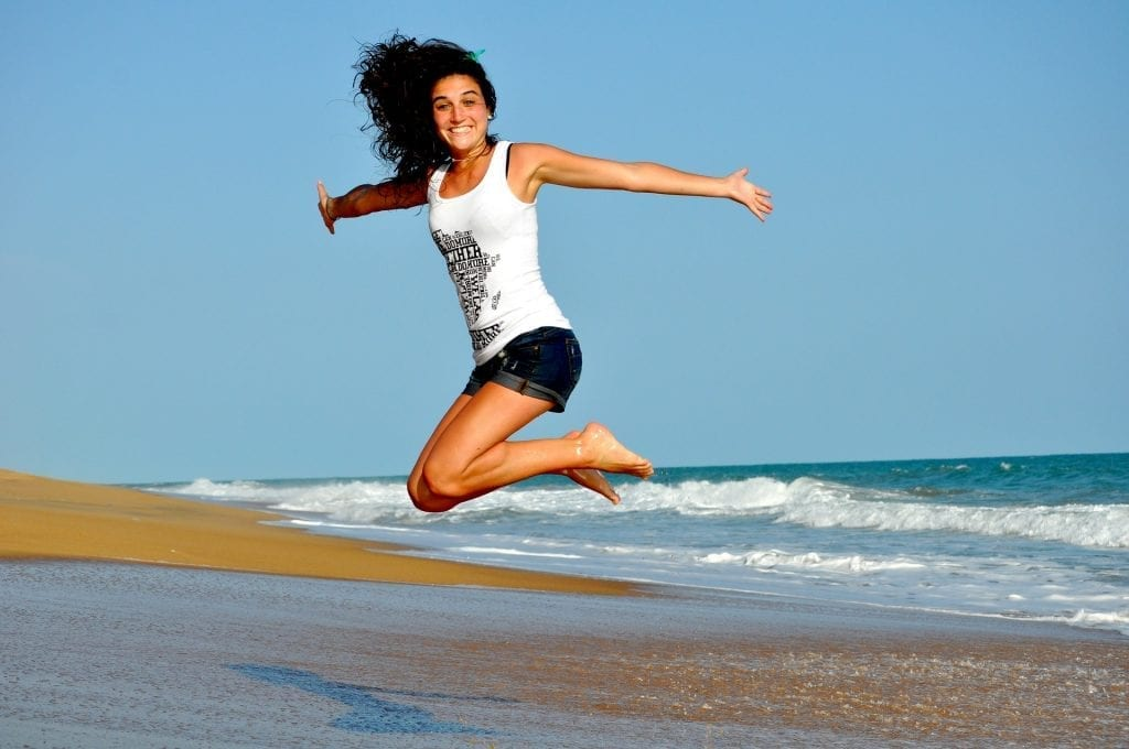 woman jumping on the beach - featured image