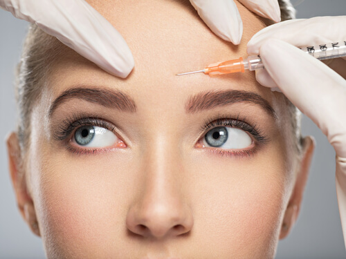 young caucasian woman getting cosmetic injection of botox in forehead-img-blog