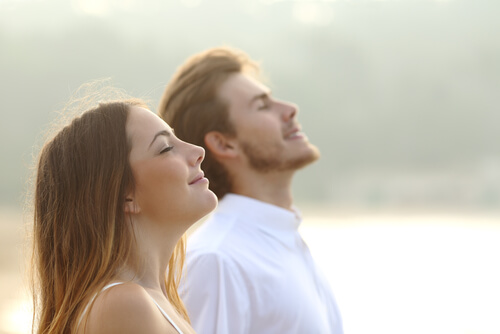Profile of a couple of man and woman breathing deep fresh air together at sunset-img-blog