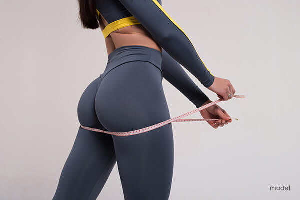 Woman holding measuring tape around her buttocks.