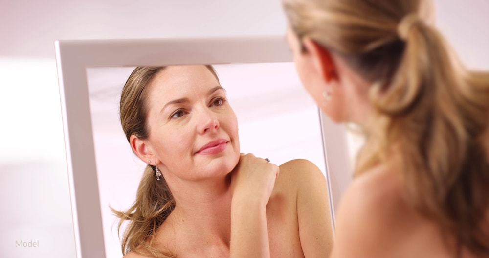 Women looking in the mirror, considering her facial rejuvenation options.