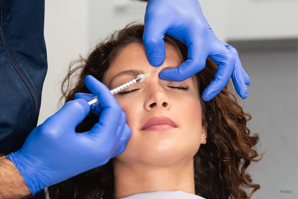 Woman getting a BOTOX® Cosmetic injection between her eyebrows.