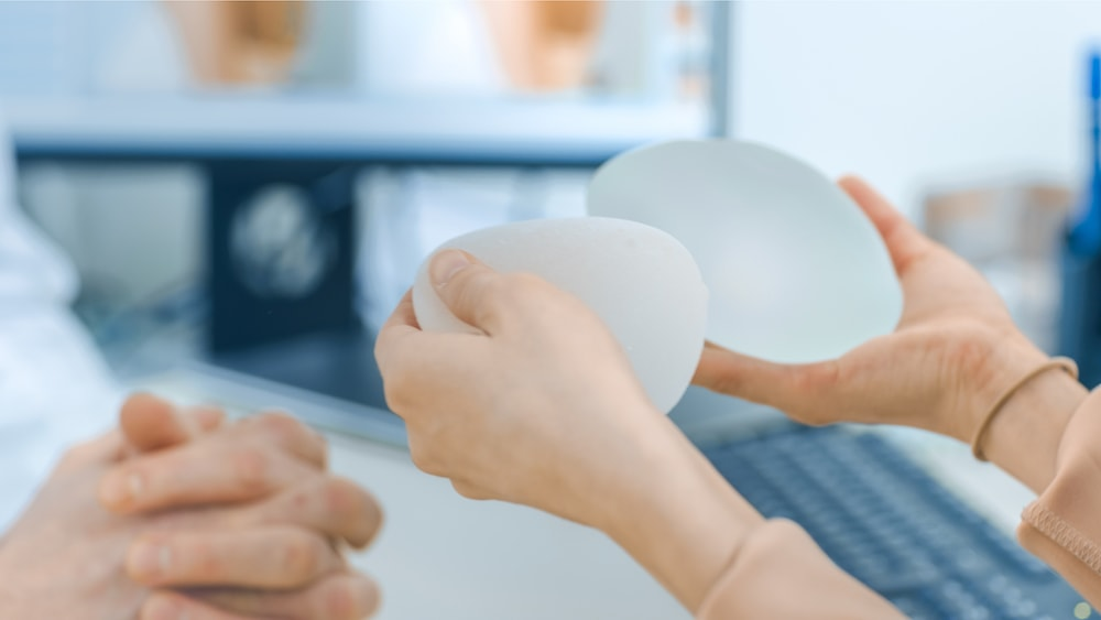 Surgeon Shows Female Patient Breast Implant Samples