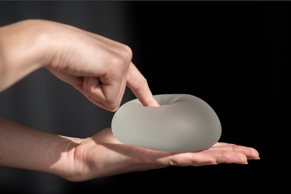 Woman pressing silicone implant. Demonstration of the reliability of silicone breast implant.