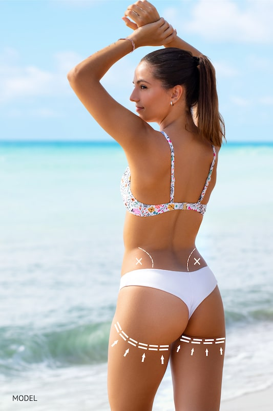 Woman standing on a beach showing off her backside curves with body contouring lines drawn on body.