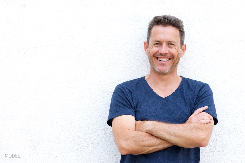 Fit man leaning against a stucco wall with folded arms.