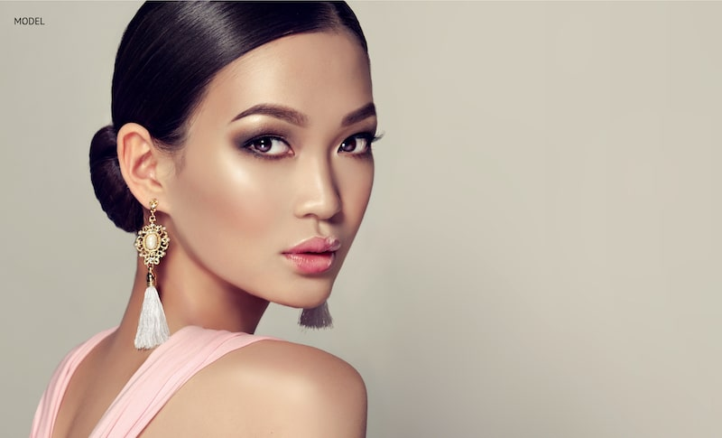 Young, beautiful Asian woman looking over her shoulder, wearing heavy gold earrings.