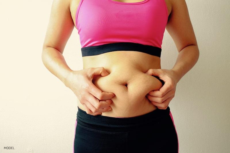 Woman grabbing her belly fat below a pink sports bra.