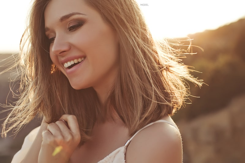 Woman with shoulder-length hair smiling with the setting sun behind