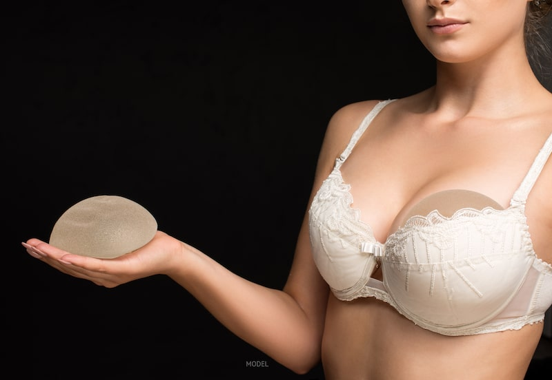 Woman in bra holding a silicone breast implant in her hand with another implant slid under her bra against a black background.